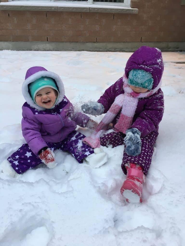 kids sitting in fresh snow
