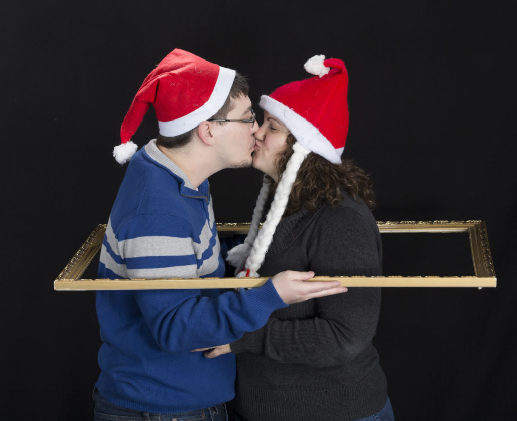 Holiday kissing in santa hat