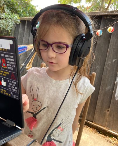 Lulu doing remote school in front of her chromebook in the backyard